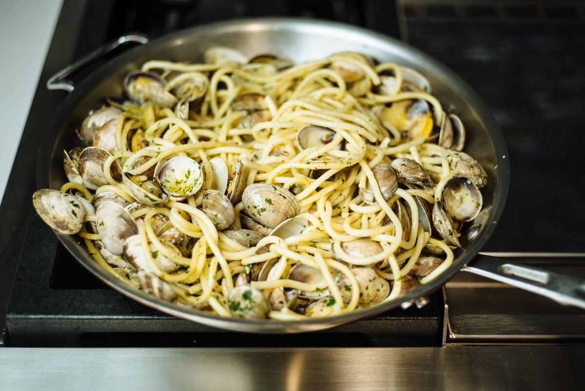 Cooking pasta with manila clams in a skillet for simple italian pasta and clams recipe from The Taste Edit