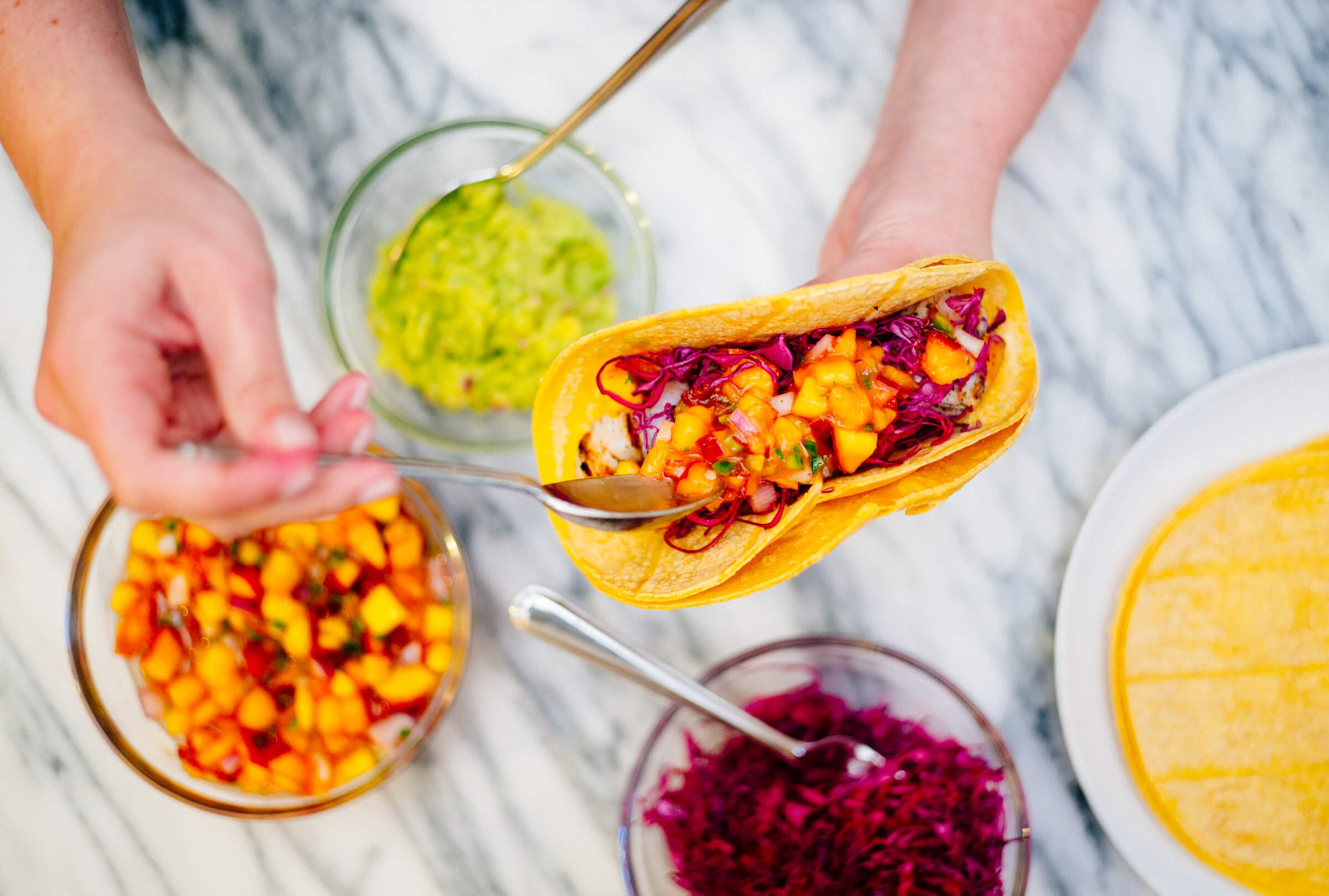 Shrimp tacos with peach salsa and toppings is perfect for summer