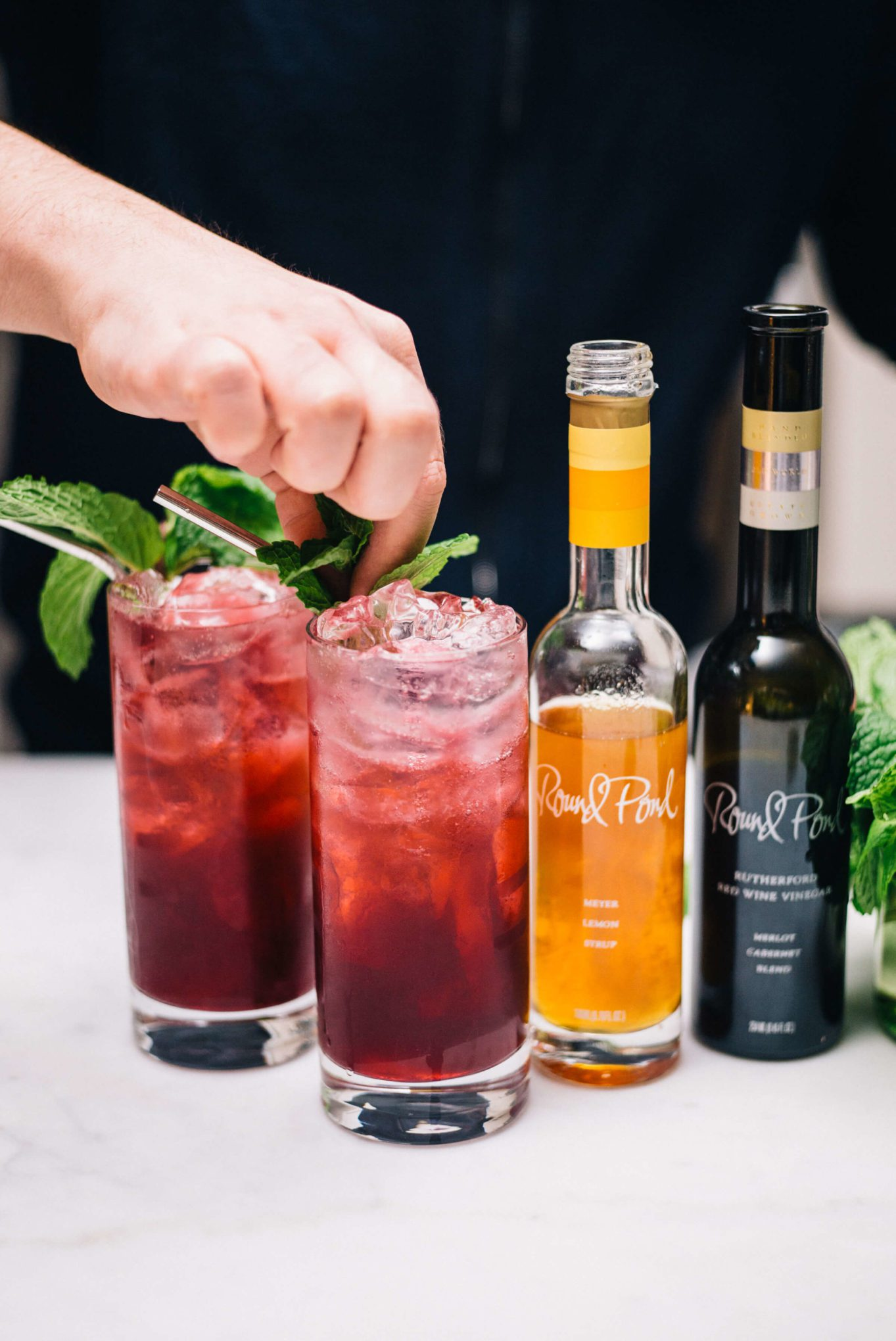 Garnishing a Blueberry Shrub Cocktail with mint | Round Pond Estate Napa Rutherford | The Taste Edit
