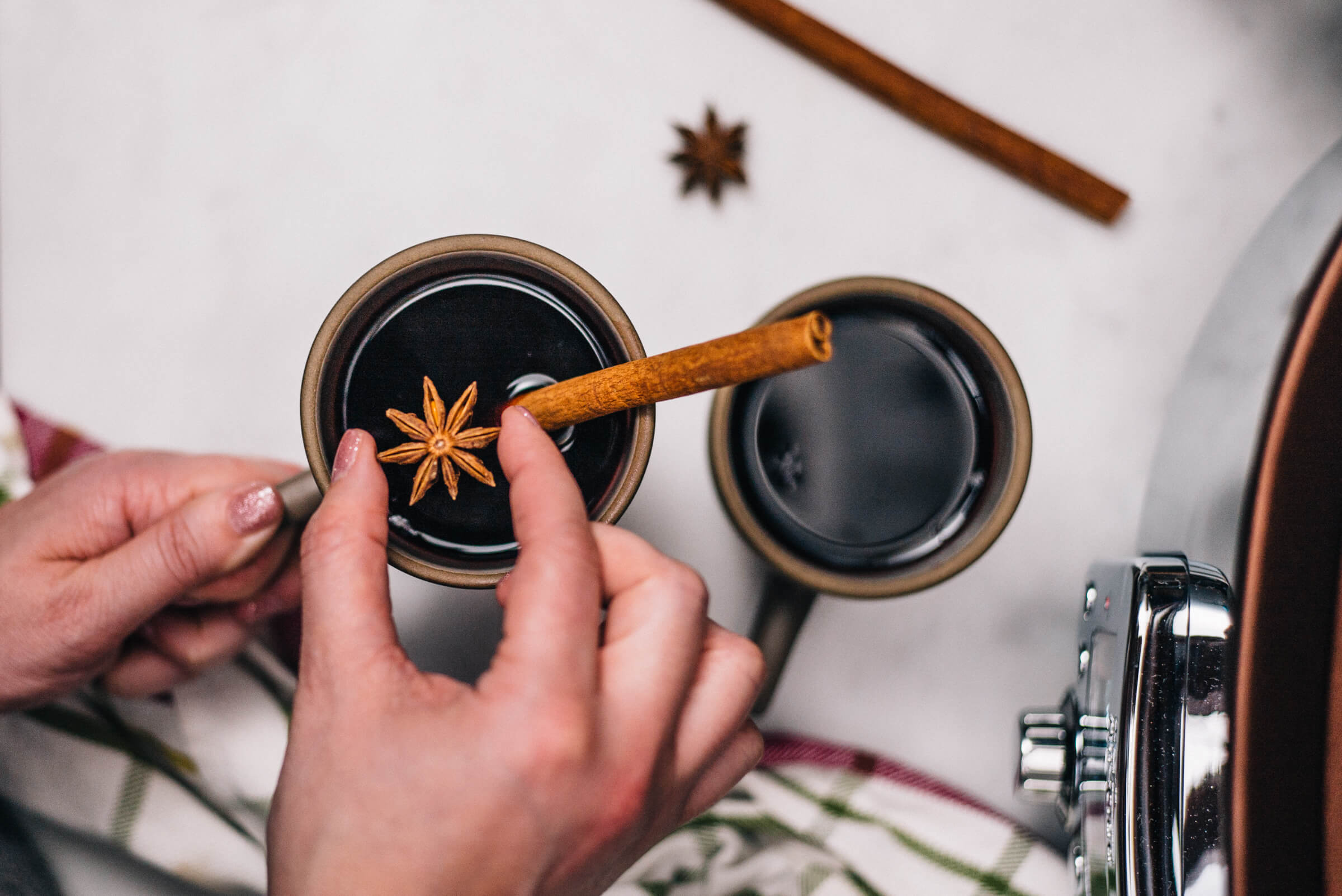 Adding cinnamon and star anise to mulled wine in an All-Clad Gourmet Slow Cooker with The Taste Edit