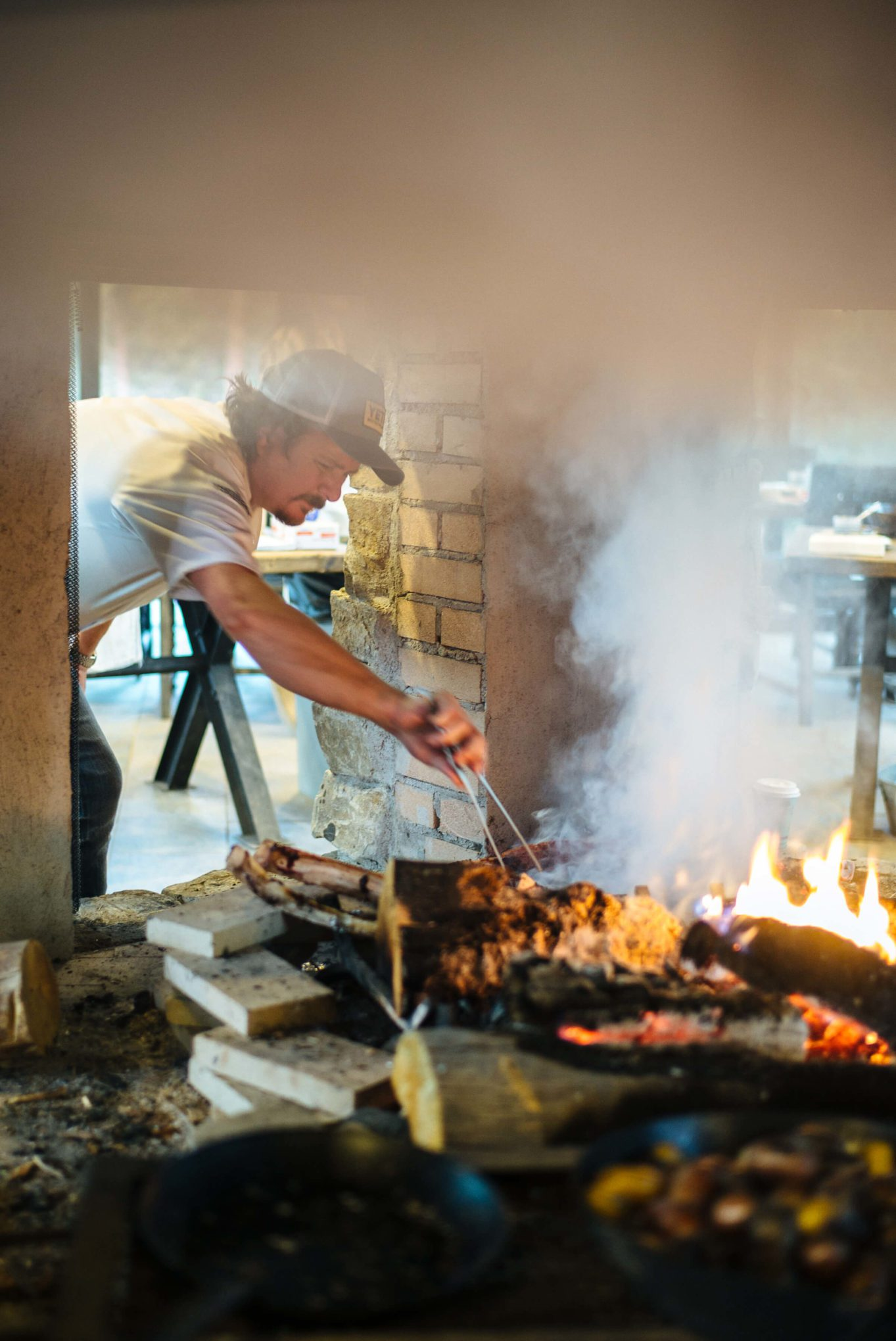 Tim Byres cooks Ribeyes directly on the coals in the live fire at cookbook live at the Resort at Paws Up, the first glamping destination in Montana, The Taste SF