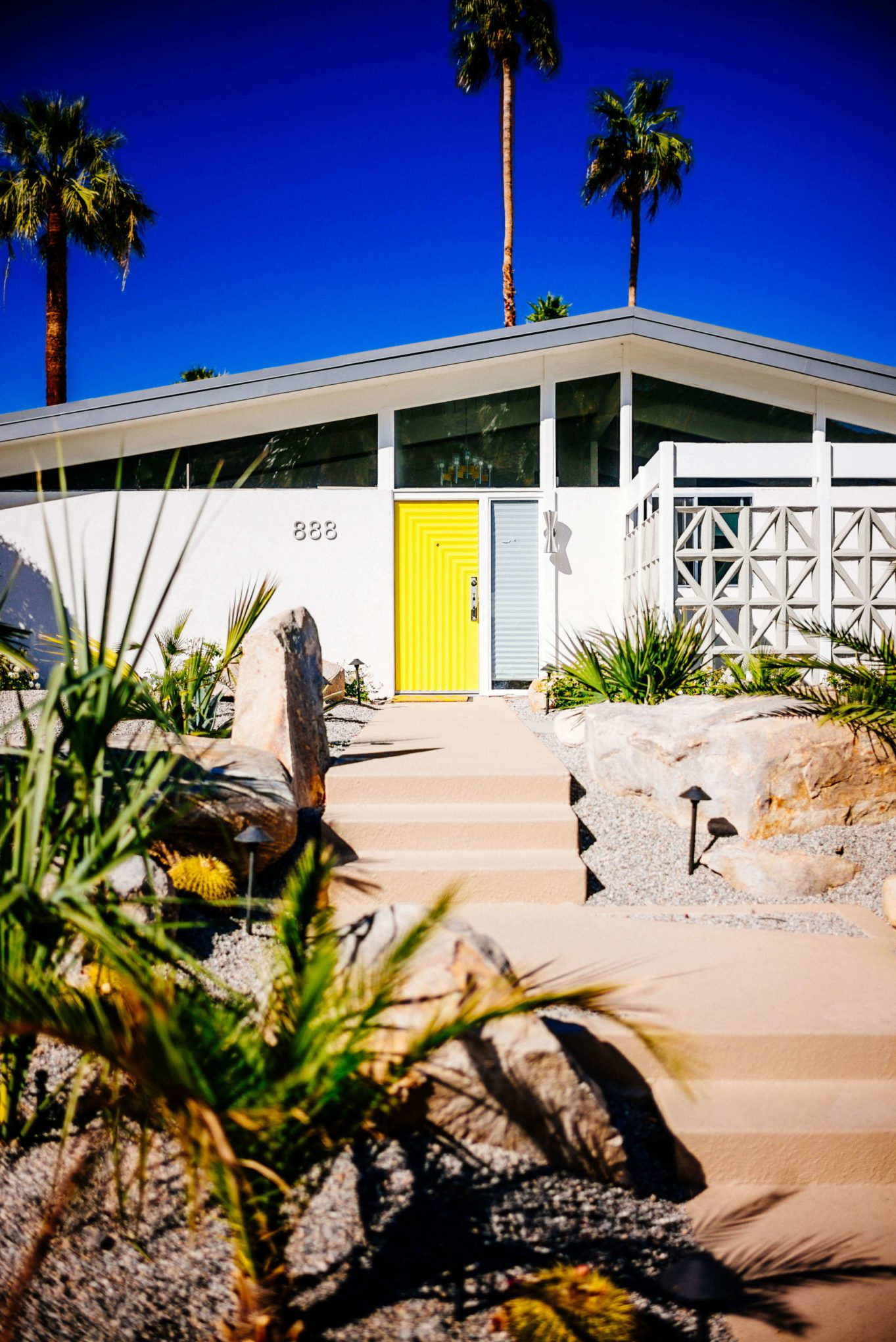 We love the bright yellow door to this house: Tour the beautiful Mid Century Homes in Palm Springs, The Taste Edit