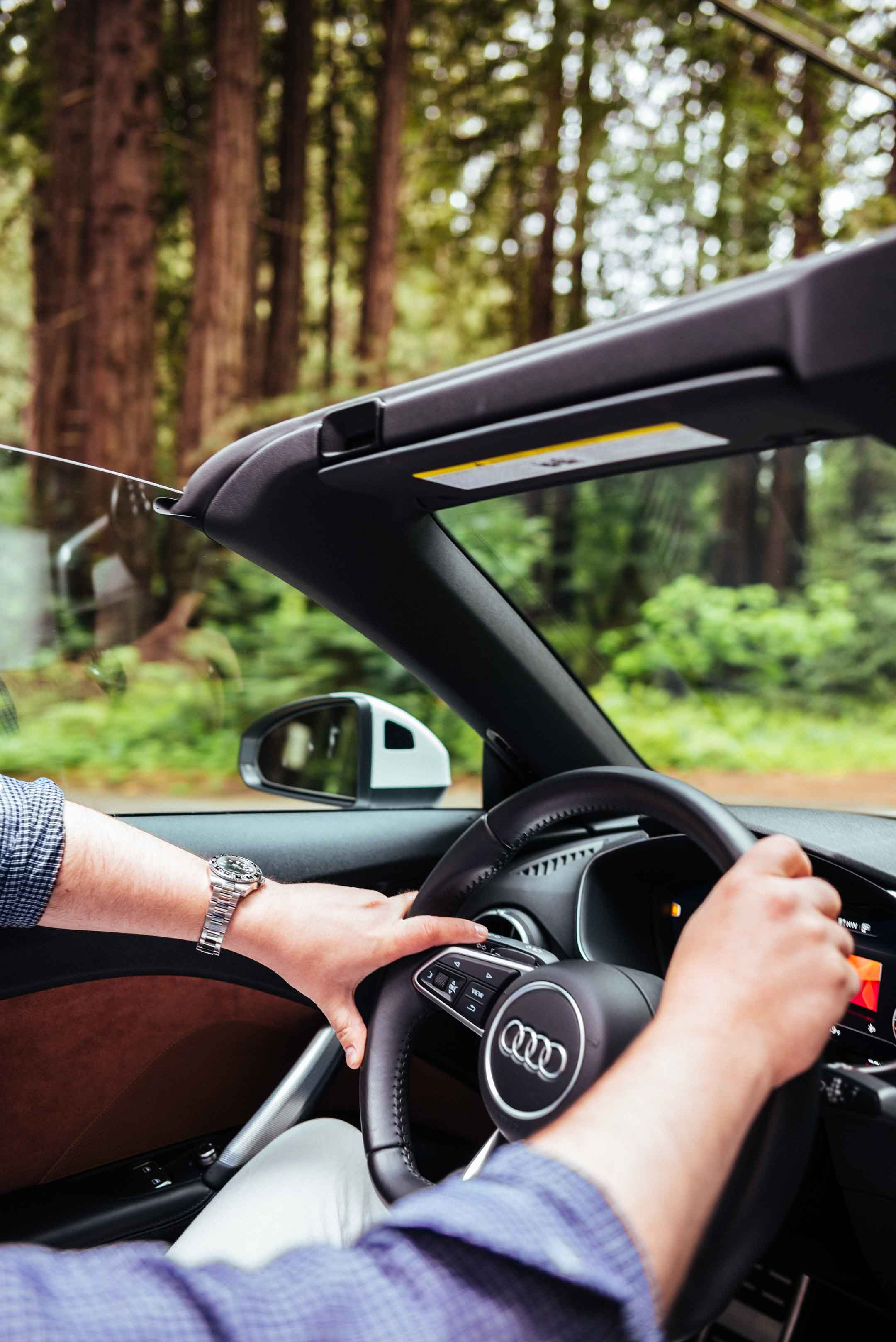 Sarah and Clayton from food and travel blog The Taste SF in San Francisco drives through the red wood forest in northern california on a day trip out of the city with Audi on Demand TT roadster convertible, wearing a GMT master and custom Isaia shir.