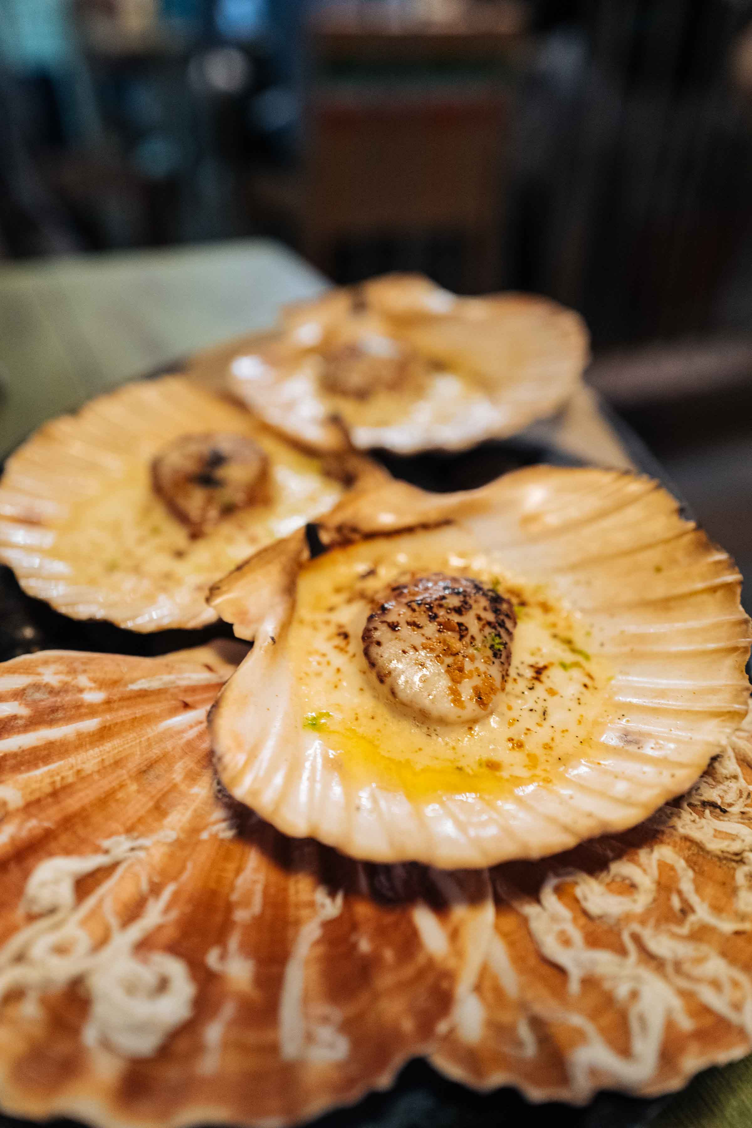 Don't miss the aged Parmigiano Reggiano foam topped grilled scallops served in their shells, in this Geneva Peruvian Restaurant | thetasteedit.com #geneva #food #switzerland #scallops #travel